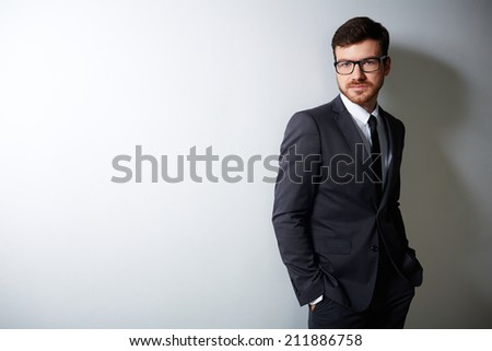 Young businessman in suit and eyeglasses looking at camera in isolation - stock photo