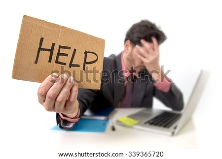 young businessman in suit and tie sitting at office desk working on computer laptop asking for help holding cardboard sign looking sad and depressed in business stress and overwork concept - stock photo