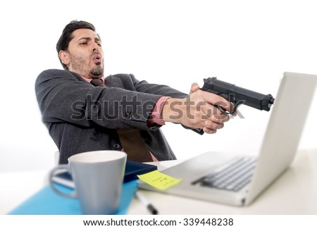 young businessman in suit and tie sitting at office desk working on computer  pointing gun to laptop in business problems stress and overwork concept - stock photo
