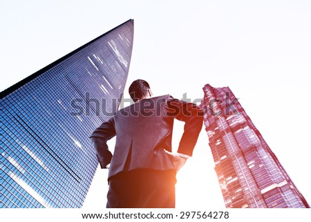 young businessman in suit looking on big skyscraper - stock photo