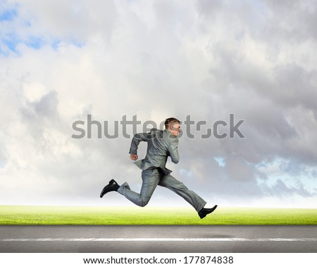 Young businessman in suit running on road - stock photo
