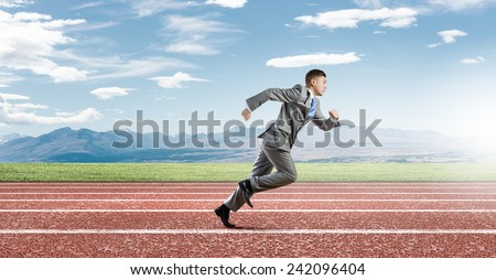 Young businessman in suit running on track