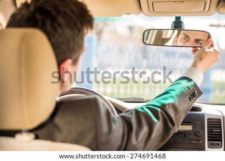 Young businessman in suit sitting in the car and looking in the front view mirror. - stock photo