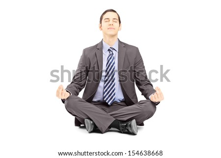 Young businessman in suit sitting on a floor and meditating isolated on white background - stock photo