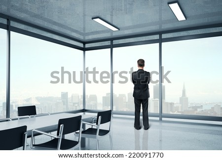 young businessman in suit standing in office