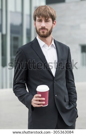 Young businessman in suit standing with coffee - stock photo