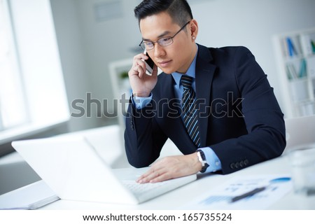 Young businessman in suit using laptop and calling in office - stock photo