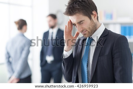 Young businessman in the office having an headache and touching his temple, stressful job and illness concept
