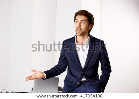 Young businessman in the suit explaining something at the office. - stock photo