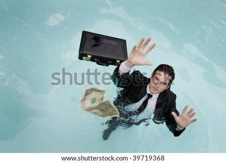 Young businessman in the water, reaching for money.