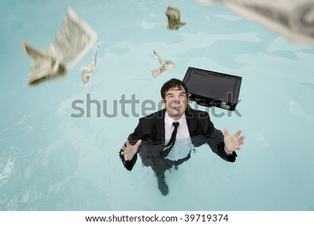 Young businessman in the water reaching for money. - stock photo