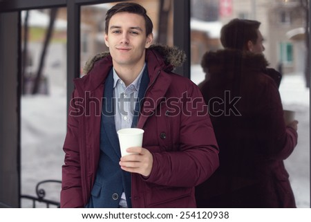 Young businessman in winter coat takes coffee to go in a cafe - stock photo