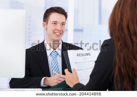 Young businessman interviewing female candidate in office - stock photo
