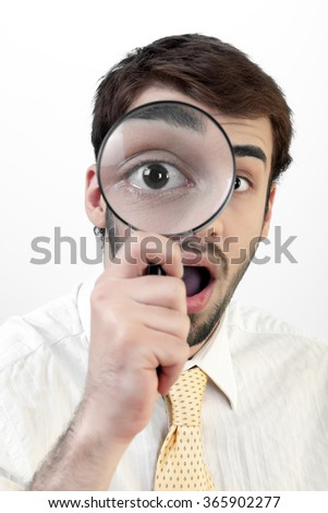 Young businessman is being shocked while he's looking from a magnifying glass.