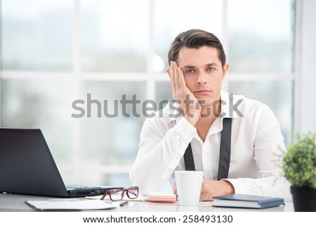 Young businessman is bored while working with computer. Office interior with big window. Man looking at camera - stock photo