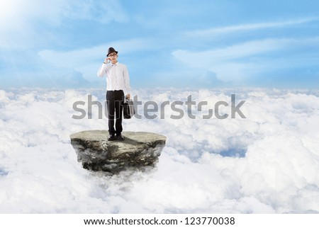 Young businessman is carrying a bag while calling above the clouds - stock photo