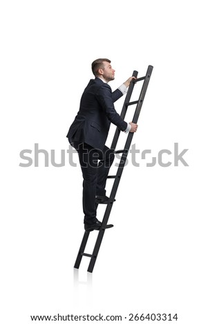 Young businessman is climbing to the career ladder. Isolated. - stock photo