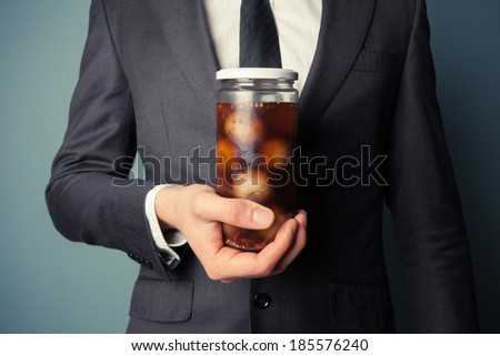 Young businessman is holding a jar of pickled onions