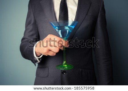 Young businessman is holding a tall cocktail glass - stock photo