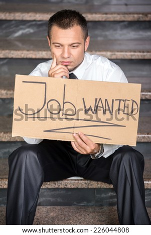 Young businessman is holding sign Wanted job, sitting on the stairs. - stock photo