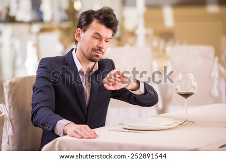 Young businessman is looking at the watch while sitting at the restaurant.