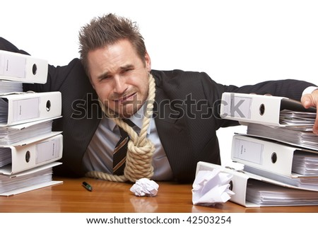 Young businessman is sitting on desk and crying because of unmanageable work. Isolated on white.