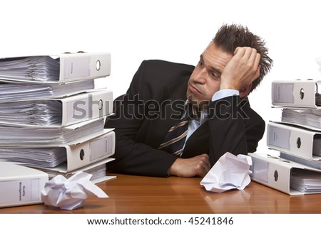 Young businessman is sitting on desk and looks frustrated on folder stack , becuase of unmanageable work. Isolated on white. - stock photo