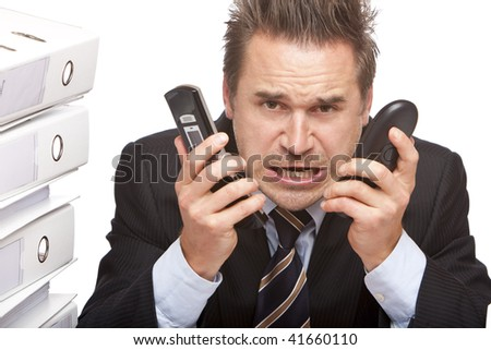 Young businessman is sitting on desk, holding two telephones and crying because of unmanageable work. Isolated on white. - stock photo