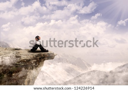Young businessman is sitting with his head down on the edge of the mountain - stock photo