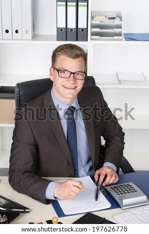 Young businessman is stamping a document in a file while sitting at the desk in the office. The man is looking to the camera.
