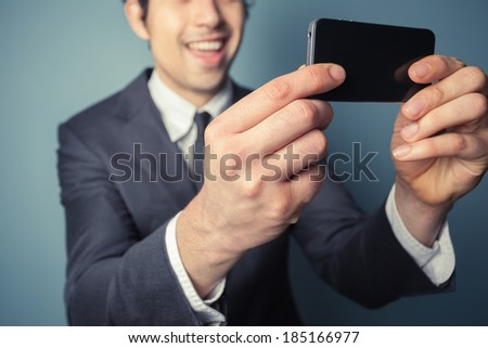 Young businessman is taking a selfie with his smart phone