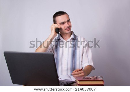 Young businessman is talking on a smartphone, at the workplace in the office
