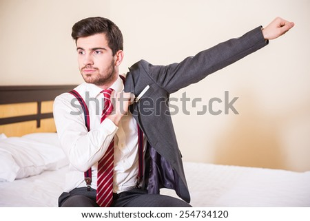 Young businessman is wearing jacket in the room at the hotel. - stock photo