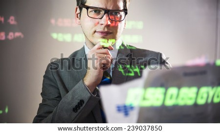 young businessman joyfully reading documents on the background Stock Exchange figures - stock photo