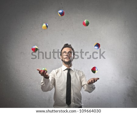 Young businessman juggling - stock photo