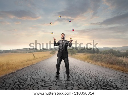 Young businessman juggling on a country road - stock photo