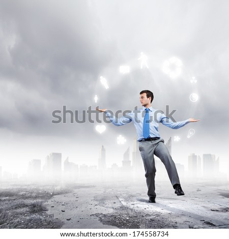 Young businessman juggling with conceptual symbols against city background