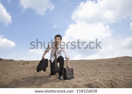 Young businessman kneeling in the desert and holding a briefcase - stock photo