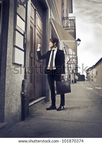 Young businessman knocking at an entrance door - stock photo