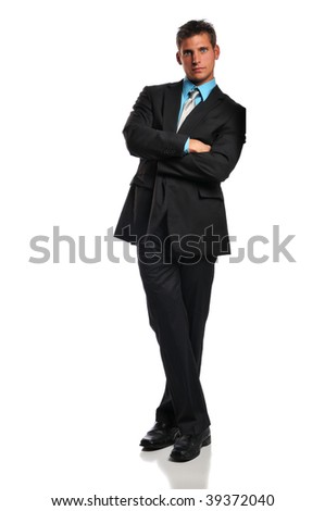 Young businessman leaning against a white wall