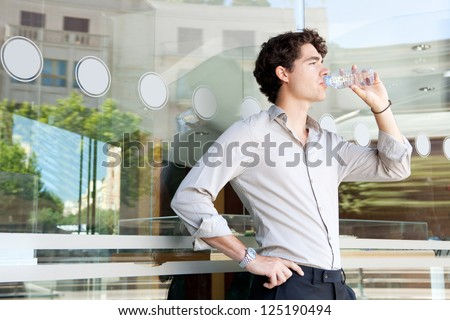 Young businessman leaning on an office building glass window drinking from a bottle of mineral water, with reflections of the city behind him. - stock photo
