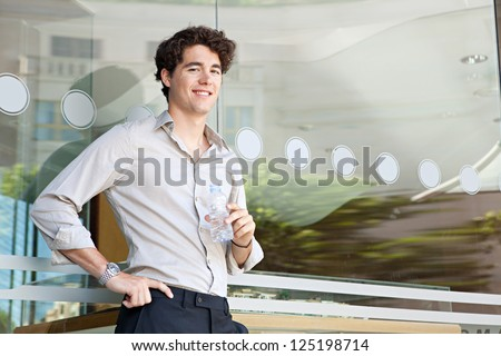 Young businessman leaning on an office building glass window holding a bottle of mineral water, with reflections of the city behind him. - stock photo