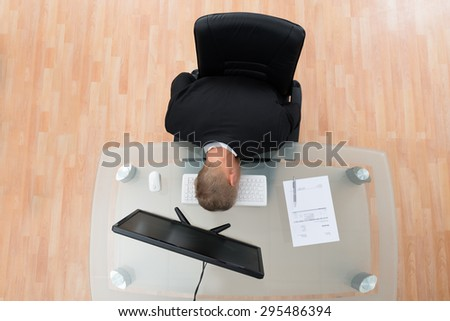 Young Businessman Leaning On Computer Keyboard At Desk - stock photo