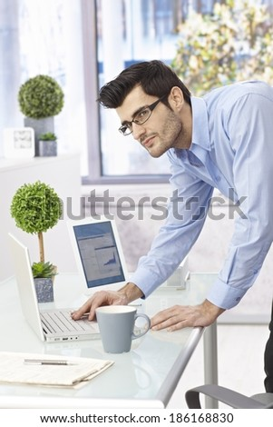 Young businessman leaning on desk, working with laptop computer, looking away. - stock photo