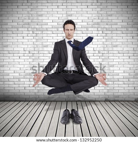 young businessman levitating in yoga position, meditation - stock photo