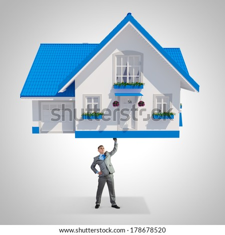 Young businessman lifting huge model of house above head - stock photo