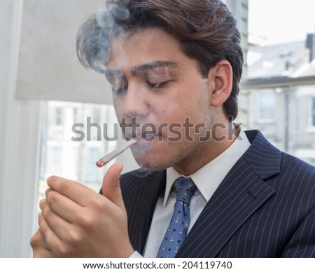Young businessman lighting up a cigarette with a lighter in his cupped hands puffing smoke while standing in an urban office with windows - stock photo