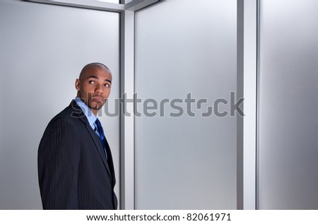 Young businessman looking anxious and worried, standing beside a window.