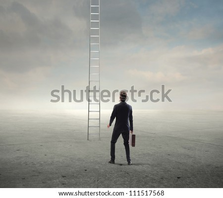Young businessman looking at a ladder - stock photo