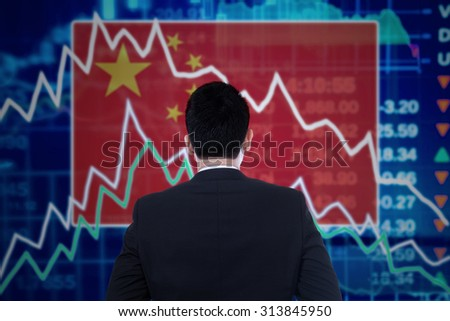 Young businessman looking at a stock market graph with a declining arrow and the chinese flag - stock photo